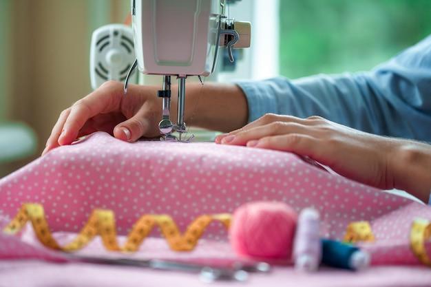 Krawcowa szyje ubrania za pomocą maszyny do szycia. proces szycia przy użyciu akcesoriów do szycia