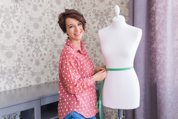 Krawcowa trzymająca taśmę miernika na manekinie w domu creative design studio