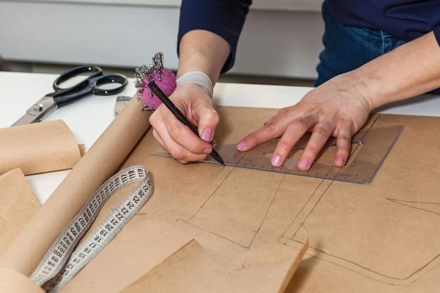 Krawcowa wycina rysunek na sukienkę nożyczkami. opracowanie stylu i projektu oraz tworzenie odzieży, usługi szycia i naprawy odzieży, koncepcja krawcowa w pracy