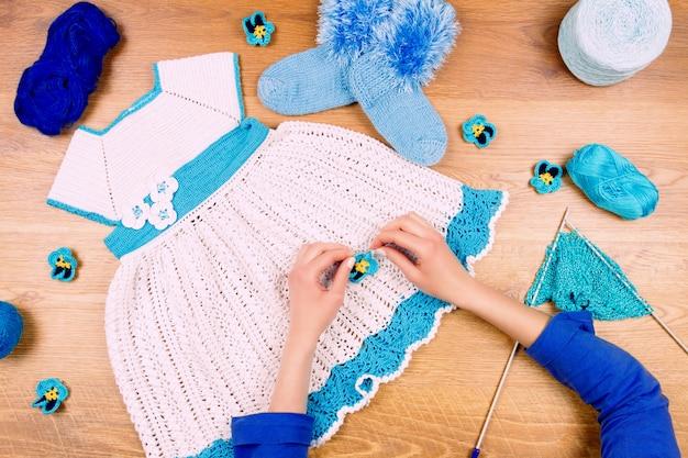 Krawcowe miejsce pracy. dziewiarska kobieta robi błękitnej sukni dla dziewczynek