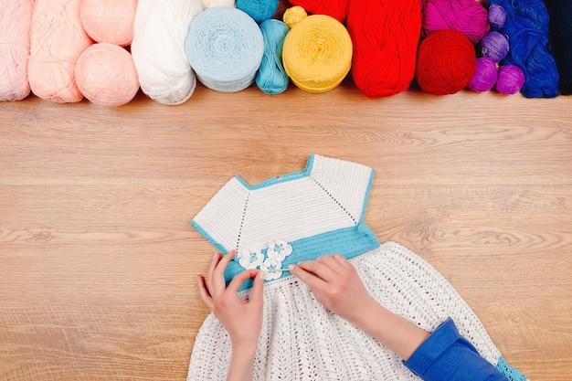 Krawcowe miejsce pracy. dziewiarska kobieta robi niebieską sukienkę dla dziewczynek z kolorowymi kulkami nici