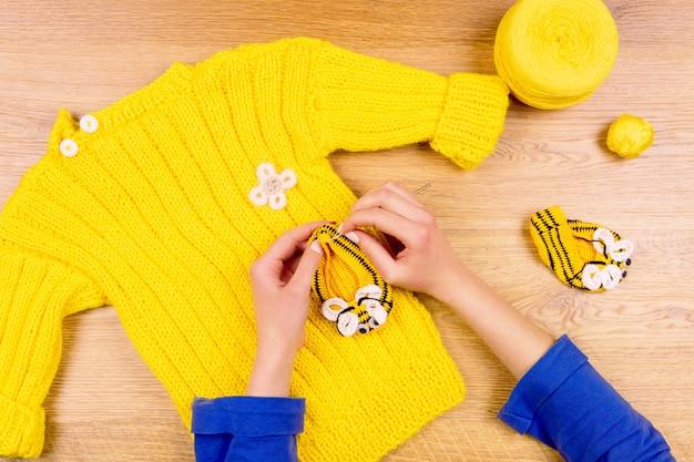Krawcowe miejsce pracy. kobiece ręce kobiety co żółte obuwie dziecięce i żółty sweter z żółtą kulką nici