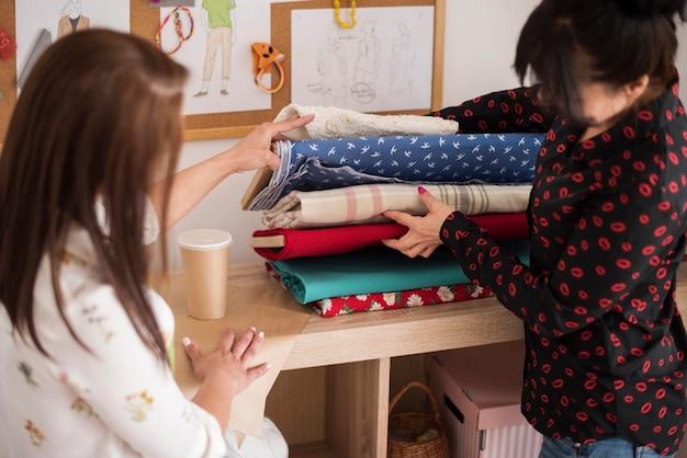 Krawcy szukający idealnego materiału na sukienkę