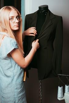 Krawiec dotykająca kurtki na manekinie