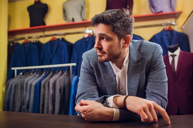Krawiec, krawiectwo. garnitur męski, krawiec w swoim warsztacie. eleganckie męskie garnitury wiszące w rzędzie. luksusowe męskie klasyczne garnitury na stojaku w eleganckim męskim butiku. ziewa zmęczony wybór