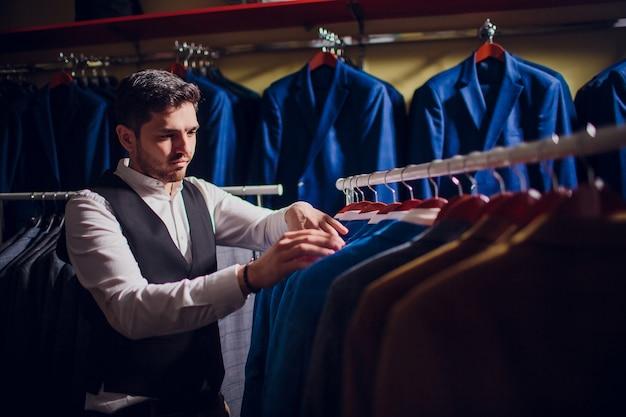 Krawiec, krawiectwo. garnitur męski, krawiec w swoim warsztacie. eleganckie męskie garnitury wiszące w rzędzie. luksusowe męskie klasyczne garnitury na stojaku w eleganckim męskim butiku.