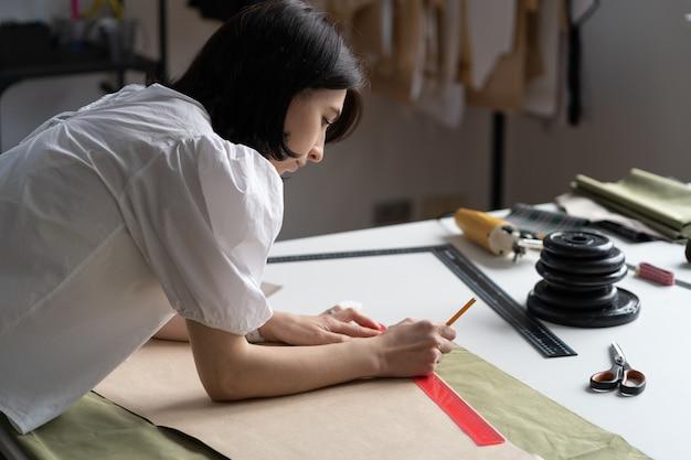 Krawiec lub krawcowa kobieta szkicuje wzory na tkaninie, aby wyciąć i uszyć młodą projektantkę w pracy