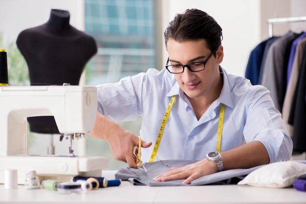 Krawiec młody człowiek pracuje nad nową odzieżą