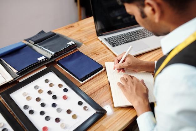 Krawiec robi listę materiałów, które wybrał do wykonania garnituru na zamówienie w atelier