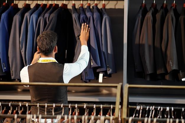 Krawiec sprawdza wykończone szyte na miarę kurtki wiszące na drążku w swoim atelier