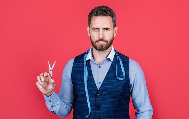Krawiec sprawia, że mężczyzna. krawiec z miarą trzymać nożyczki czerwone tło. szycie na miarę. profesjonalna krawcowa lub projektantka. sklep krawcowy. wykonuj i naprawiaj usługi.