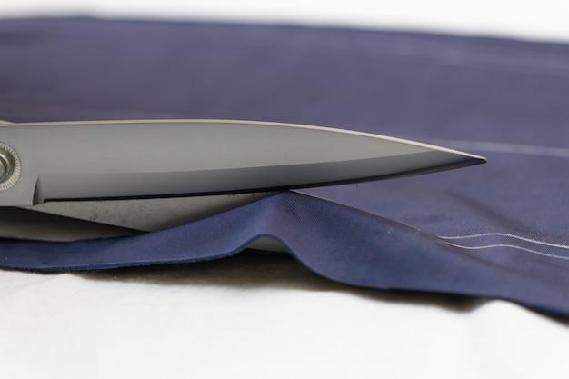 Krawiec tnie materiał nożyczkami na stole
