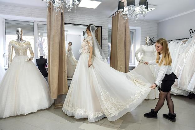 Krawiec w salonie ślubnym pomaga pannie młodej przymierzyć sukienkę
