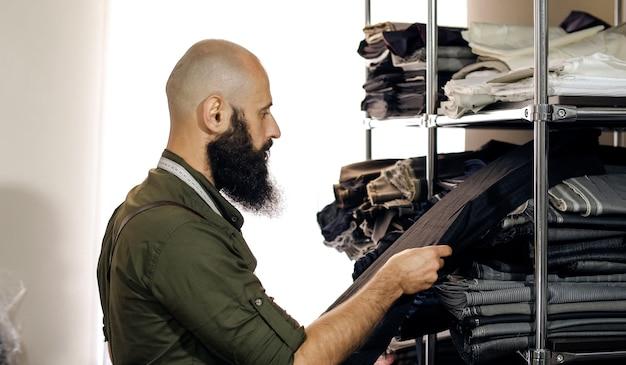 Krawiec w szwalni w pracy. jego studio to sunny. widoczne są kolorowe tkaniny, ubrania.