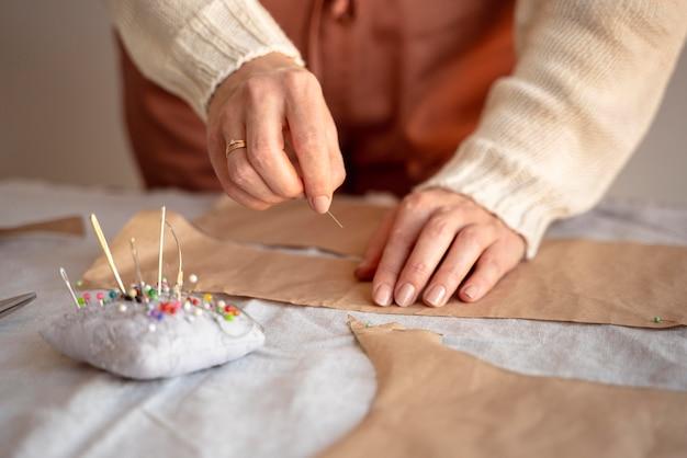 Krawiecka kobieta używa igły i nici do szycia