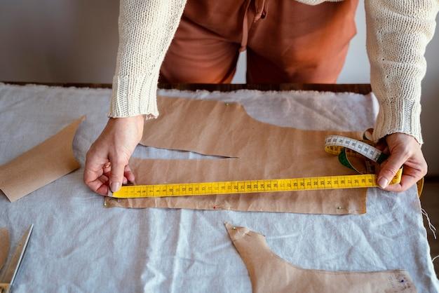 Krawiecka kobieta za pomocą linijki do pomiaru tkaniny