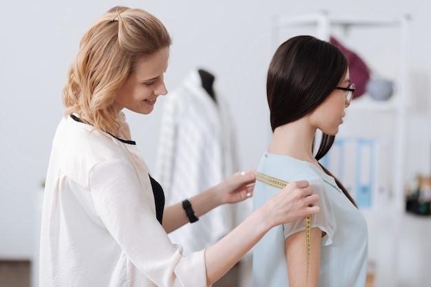 Krawiecka stojąca w atelier, trzymająca taśmę i mierząca tył brunetki w okularach.