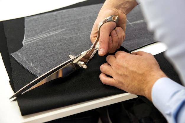 Krawieckie cięcie materiału nożycami lub nożyczkami według wzoru kredy, zbliżenie dłoni