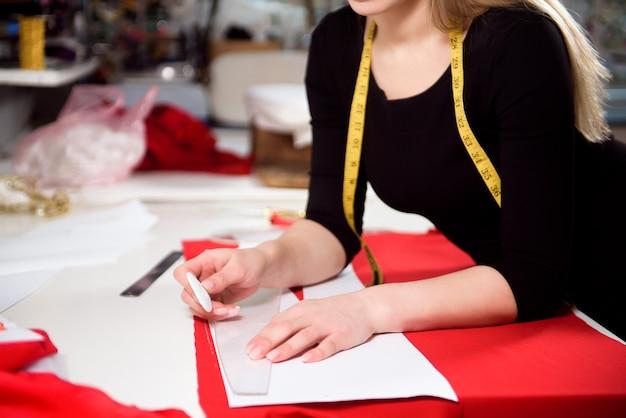 Krawieckie cięcie tkaniny na sukienkę na linii szkicu za pomocą maszyny do szycia. właściciel firmy, sklep i koncepcja przedsiębiorcy.