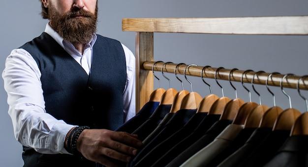 Krawiectwo krawieckie stylowy garnitur męski przystojny brodaty mężczyzna mody w klasycznym kostiumie