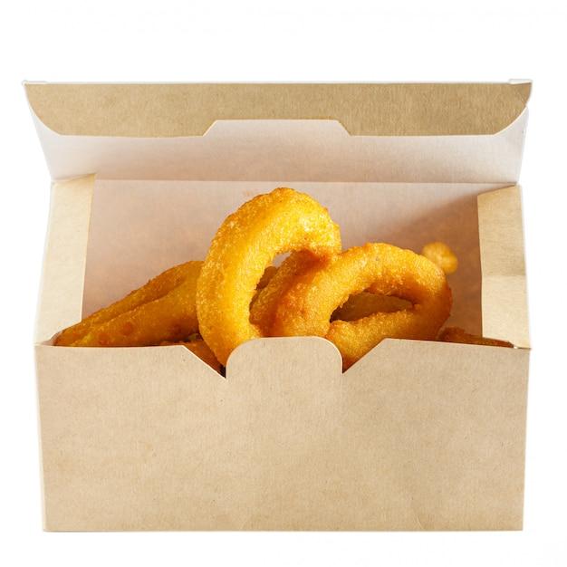 Krążki cebuli frytki w papierowym pudełku, aby przejść na biały