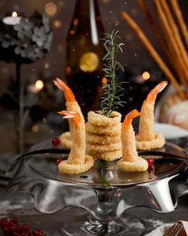 Krążki cebuli ze smażonymi krewetkami na stole