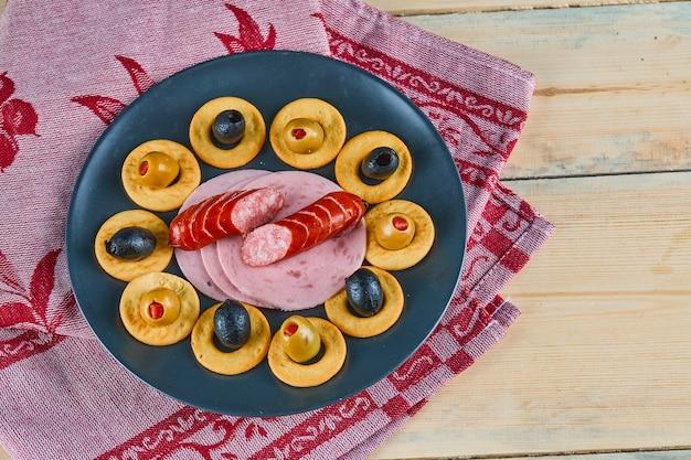 Krążki i plasterki kiełbasek z oliwkami na talerzu ceramicznym z różowym obrusem.
