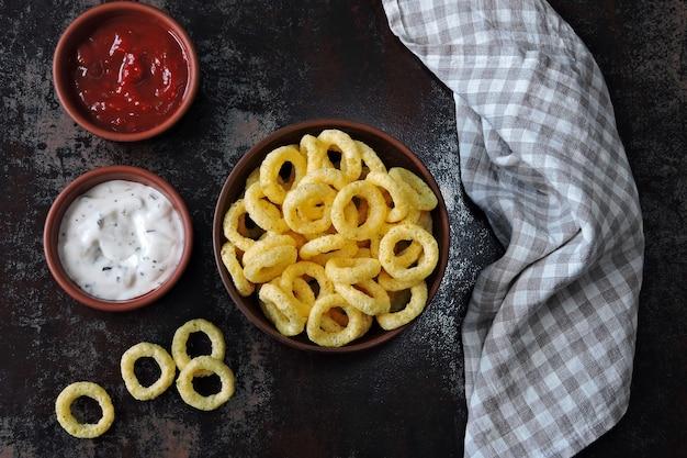 Krążki kukurydziane w misce z sosem czerwono-białym. flat lay.