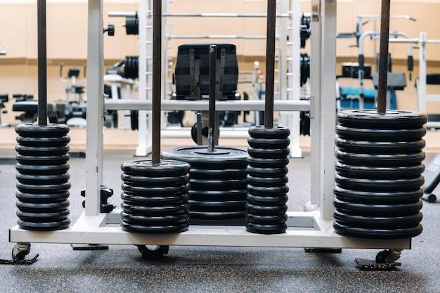 Krążki sztangi ułożone rzędami na siłowni.