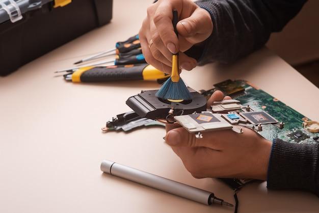 Kreator naprawia laptopa za pomocą narzędzi i rąk