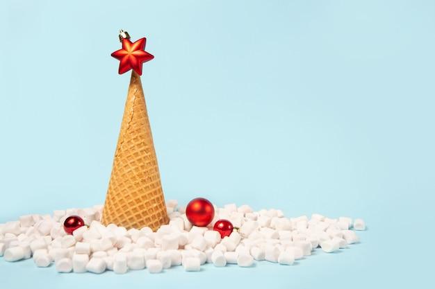 Kreatywna choinka wykonana z lodowego rożka waflowego. śnieg jest zrobiony z pianek marshmallow.