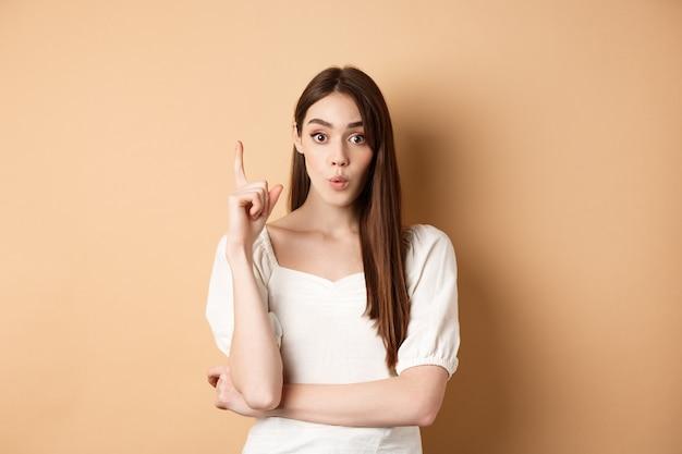 Kreatywna dziewczyna podsuwa pomysł, podnosi palec w geście eureki, wypowiada swój plan, ma sugestię lub rozwiązanie, stoi w sukience na beżowym tle.