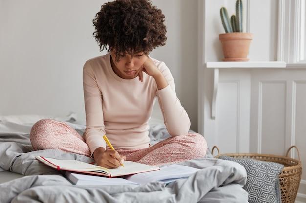 Kreatywna dziewczyna pozuje w domu w wygodnym łóżku
