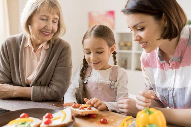 Kreatywna dziewczyna robi kanapki z warzywami na śniadanie wśród matki i babci