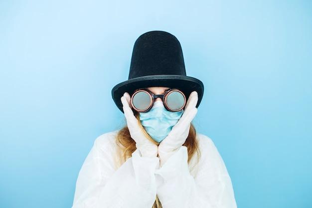 Kreatywna dziewczyna w białej szacie, masce medycznej, okularach i kapeluszu na niebieskiej ścianie. samoizolacja podczas kwarantanny koronawirusa. epidemic covid-2019.