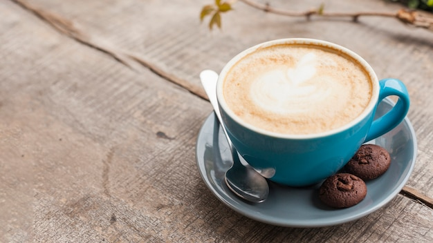 Kreatywna filiżanka kawy latte z dwoma pieczonymi ciasteczkami na drewnianym biurku