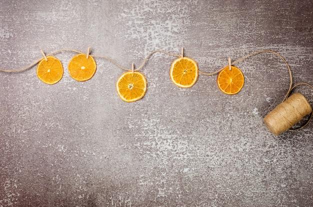 Kreatywna girlanda wykonana z domowej roboty suszonych plastrów pomarańczy z spinaczami do bielizny na sznurku konopnym. boże narodzenie i nowy rok, zimowa kompozycja. widok z góry, układ płaski, przestrzeń do kopiowania