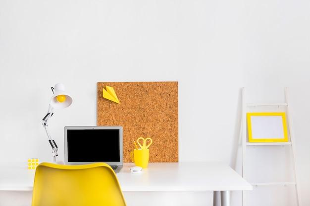 Kreatywna jasna szafka z żółtym krzesłem i deską korkową