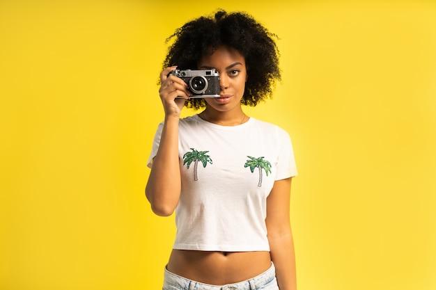 Kreatywna kobieta-fotograf robi zdjęcia, odizolowane na żółto.