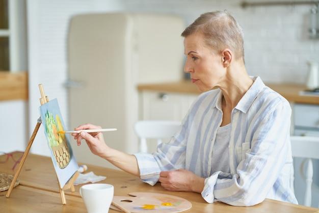 Kreatywna kobieta w średnim wieku maluje obraz w domu, siedząc przy drewnianym stole w kuchni