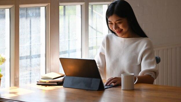 Kreatywna kobieta za pomocą / pisania na komputerze, siedząc przed rośliną doniczkową i książkami przy nowoczesnym drewnianym stole z wygodnym salonem i oknami jak