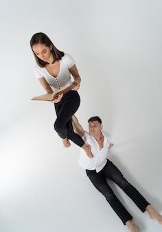 Kreatywna kompozycja kobiety siedzącej na dłoni mężczyzny i czytając książkę. koncepcja wsparcia, opieki i edukacji.