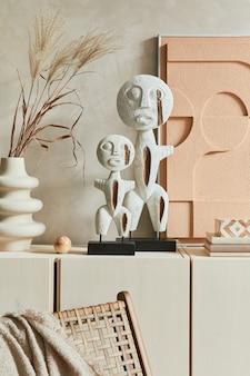 Kreatywna kompozycja nowoczesnej beżowej aranżacji wnętrza salonu z dwiema zaprojektowanymi rzeźbami, malowaniem struktur, beżowym drewnianym kredensem i osobistymi dodatkami inspirowanymi boho. szablon.