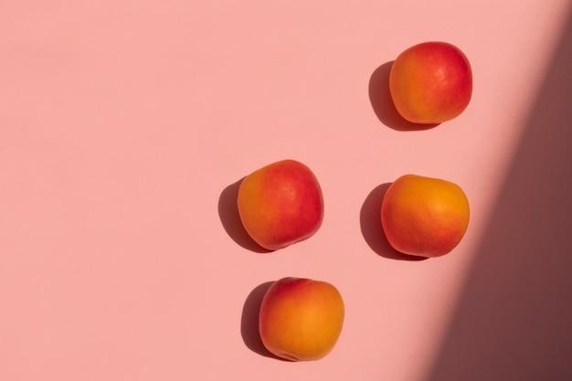 Kreatywna kompozycja owocowa świeżych moreli na różowym tle z mocnymi cieniami