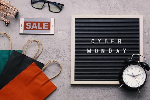 Kreatywna kompozycja promocyjna z płaskim świeckim tekstem sprzedaży cyber poniedziałek na tablicy z budzikiem