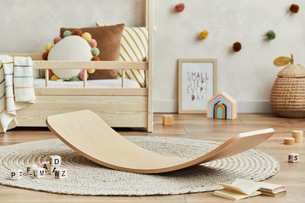 Kreatywna kompozycja przytulnego skandynawskiego wnętrza pokoju dziecięcego z łóżkiem, pluszowymi zabawkami, deską balansową i tekstylnymi wiszącymi dekoracjami. ściana kreatywna, na podłodze parkiet dywan. szablon.
