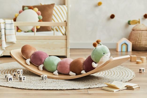 Kreatywna kompozycja przytulnego wnętrza dziecięcego pokoju scandi z pluszową gąsienicą na desce balansowej, drewnianymi zabawkami i tekstylnymi dekoracjami. ściana neutralna. detale. szablon.