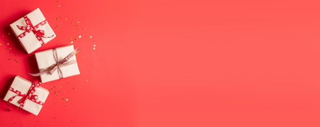 Kreatywna kompozycja pudełko z dekoracją złotych gwiazd, kulki na czerwonym tle.