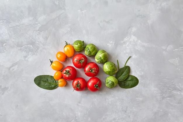 Kreatywna kompozycja różnych pomidorów i liści szpinaku