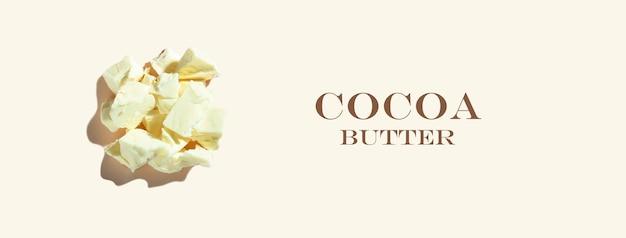 Kreatywna kompozycja składników ze zdrowym organicznym masłem kakaowym na tle kości słoniowej